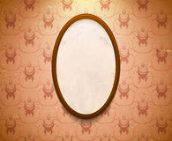 Elliptic wooden frame. On the wall with aged wallpaper Stock Image