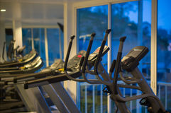 Elliptical cross trainers in a fitness gym at evening. Elliptical cross trainers in a fitness gym Stock Photos
