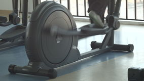 Elliptical exercises in gym stock video