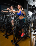 Elliptical walker trainer man and woman at black gym Royalty Free Stock Images