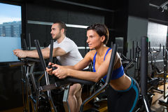Elliptical walker trainer man and woman at black gym Royalty Free Stock Image