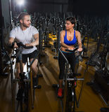 Elliptical walker trainer man and woman at black gym Royalty Free Stock Photos