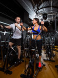 Elliptical walker trainer man and woman at black gym Stock Photo