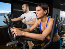 Elliptical walker trainer man and woman at black gym Stock Images