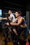 Elliptical walker trainer man and woman at black gym Stock Image