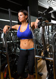 Elliptical walker trainer womman posing relaxed at gym. Elliptical walker trainer woman posing at black gym relaxed after aerobics exercise Stock Photo