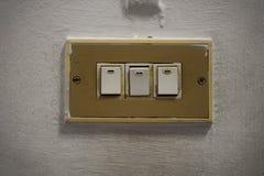 Elljusströmbrytare för tre tappning på den gamla väggen arkivfoton