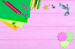 Ellow och gräsplan ritar, tuschpennor, brevpapper, gemmar, brevpapper spikar, klädde med filt och leenden på rosa träbakgrund Royaltyfri Foto