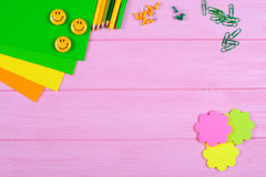 Ellow und grüne Bleistifte, Filzstifte, Briefpapier, Büroklammern, Briefpapiernägel, Filz und Lächeln auf rosa hölzernem Hintergr Lizenzfreie Stockfotos