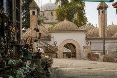 The street view of the Ketendji Omer Pasha Mosque and its social building complex with copperware exhibit in the foreground. royalty free stock image