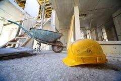 Elmetti protettivi e carrello sul pavimento di calcestruzzo Immagini Stock