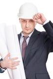 Elmetto protettivo bianco da portare dell'assistente tecnico con le cianografie Fotografie Stock