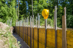 Elmetto protettivo giallo che pende dai pannelli di legno di sostegno fotografia stock libera da diritti