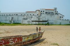 Elmina,加纳- 2014年2月13日:与木渔船和海滩的Elmina城堡在前景 免版税库存图片