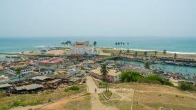Elmina,加纳- 2014年2月13日:五颜六色的木渔船和历史殖民地城堡在非洲镇Elmina 库存照片