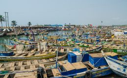 Elmina,加纳- 2014年2月13日:五颜六色的被停泊的木渔船在非洲港口镇Elmina 库存图片