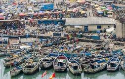Elmina,加纳- 2014年2月13日:五颜六色的被停泊的木渔船在非洲港口镇Elmina 免版税库存图片