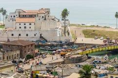 Elmina, Γκάνα - 13 Φεβρουαρίου 2014: Ζωηρόχρωμα ξύλινα αλιευτικά σκάφη και ιστορικό αποικιακό κάστρο στην αφρικανική πόλη Elmina Στοκ Εικόνα