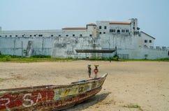 Elmina, Ghana - 13. Februar 2014: Elmina-Schloss mit hölzernem Fischerboot und Strand im Vordergrund lizenzfreie stockbilder