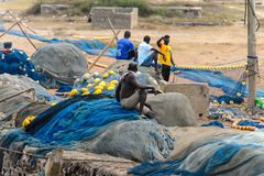 Unidentified Ghanaian man sits in the fishing net from behind i. ELMINA, GHANA -JAN 18, 2017: Unidentified Ghanaian man sits in the fishing net from behind in royalty free stock photo