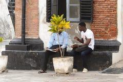 Unidentified Ghanaian men talk about something behind the flowe. ELMINA, GHANA -JAN 18, 2017: Unidentified Ghanaian men talk about something behind the flowerpot royalty free stock image