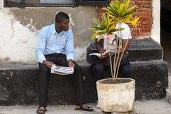 Unidentified Ghanaian men talk about something behind the flowe. ELMINA, GHANA -JAN 18, 2017: Unidentified Ghanaian men talk about something behind the flowerpot stock photos