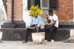 Unidentified Ghanaian men talk about something behind the flowe. ELMINA, GHANA -JAN 18, 2017: Unidentified Ghanaian men talk about something behind the flowerpot royalty free stock photos