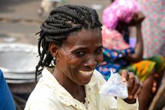 Unidentified Ghanaian woman with braids smiles in Elmina port. ELMINA, GHANA -JAN 18, 2017: Unidentified Ghanaian woman with braids smiles in Elmina port stock photos