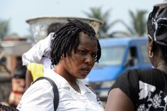 Unidentified Ghanaian woman with braids in white shirt frowns i. ELMINA, GHANA -JAN 18, 2017: Unidentified Ghanaian woman with braids in white shirt frowns in stock photos