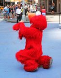 Elmo In NYC. A man in Elmo costume takes a photo in Times Square, NY royalty free stock photography