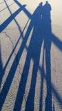 Elongated cienie dwa ludzie na betonowej ulicy powierzchni na bardzo pogodnym letnim dniu, zdjęcie stock