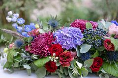 Free Elongated Floral Arrangement In Vintage Metal Vase. Table Setting. Blue And Red Color. Gorgeous Bouquet Of Different Stock Photo - 125771120