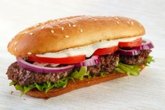 Elongated hamburger. (burger sandwich) with three grilled patties , lettuce ,  red onion , tomato and mayonnaise Royalty Free Stock Image