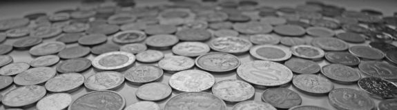 An elongated image with coins from different currencies in black and white stock photography