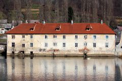 Elongated Old Dilapidated Apartment Building With Cracked Facade And New Roof Tiles Built On River Bank Surrounded With Houses And Royalty Free Stock Photo