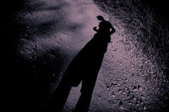 Elongated shadow of a man on gravel Stock Image