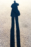 Elongated Shadow of a Person Standing on the Road Royalty Free Stock Photos