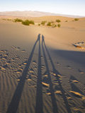 Elongated Shadow of Two People On Sand Stock Images