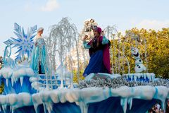 Elsa and Anna of. Elsa and Anna as well as Olaf from the popular computer-animated musical fantasy-comedy are waving atop a beautiful blue and white snowy float Royalty Free Stock Photography