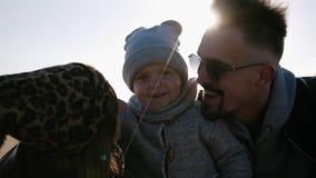 Elterlicher Kuss für Kind im Sonnenlicht, junges verheiratetes Paar der guten Laune mit Sohn im Freilicht, glückliches Kindstehen stock video footage