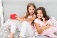 Elterliches Beratungs Internet-Surfens und -abwesenheit Smartphone-Internet-Zugang Mädchenschwestern tragen den Pyjama, der mit b lizenzfreie stockbilder