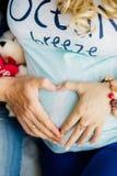 Eltern übergibt die Herstellung des Herzens auf Bauch von Stockbild
