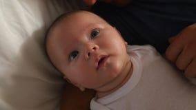Eltern, die in Bett-Umarmungsbaby-Tochter liegen stock video