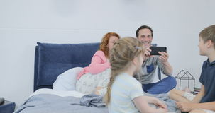 Eltern, die das Video von den Kindern spielen zusammen sitzend auf Bett im Schlafzimmer, glückliche Familie zusammen verbringt Ze stock footage