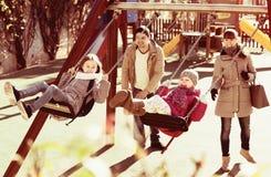 Eltern, die das wenig Tochterschwingen aufpassen Lizenzfreies Stockfoto