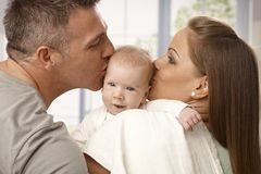 Eltern, die den Kopf des Babys küssen Lizenzfreie Stockfotos