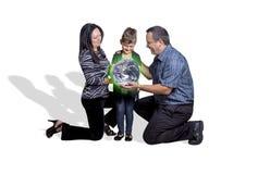 Eltern, die eine grüne Erde zu ihrem Kind überreichen Lizenzfreie Stockfotos