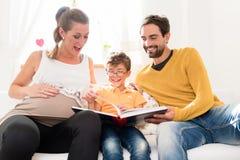 Eltern, die ihre Bilder des erstgeborenen Sohns im Familienalbum zeigen Lizenzfreie Stockfotos