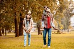 Eltern, die ihre Kinder geben, die ein Doppelpol in reiten stockfotos