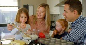 Eltern, die ihre Tochter unterrichten, das Ei beim Backen von 4k zu brechen stock video